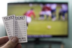 A man`s hand holds bookmakers` tickets against the backdrop of a television set running football royalty free stock photography