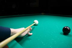 Man's hand holds a cue for striking the white cue ball. Russian. Pyramid (Russian billiard, pyramid billiards), cue sport Stock Photo