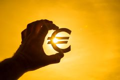 A man`s hand holds the euro symbol against the light of the sun. royalty free stock photos