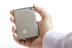 Man`s hand holds a 2.5 inch hard drive. Stock Images