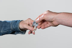 A man´s hand holds a key-pair,  on a grey background Royalty Free Stock Photo