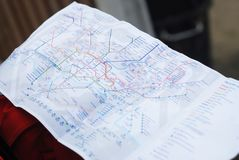 The man`s hand holds the map of the subway trains Underground to locate appointment. Close Up Map. The man`s hand holds the map of the subway trains Underground Stock Photography