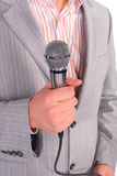 Man`s hand holds microphone Stock Images
