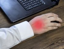A man`s hand holds a mouse while working at a computer, a pain in his hand, a close-up stock images