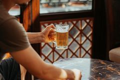 Man`s hand holds a mug of beer. Mug in the center of the photo. A pint of light beer. Alcohol, beer stock photo