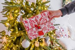 A man`s hand holds out a gift under the tree . cozy Christmas decor garland bokeh. new year 2019 stock images