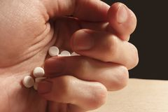 Man`s hand holds a pile of white pills stock photography