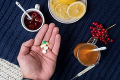 A man`s hand holds a pill. Still life of tea with lemon, tablets and thermometer, jam and berries. The concept of treating colds.  Royalty Free Stock Images