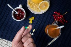 A man`s hand holds a pill. Still life of tea with lemon, tablets and thermometer, jam and berries. The concept of treating colds.  Royalty Free Stock Photography
