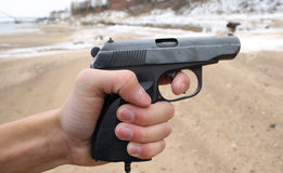 The man's hand holds a pistol Stock Images