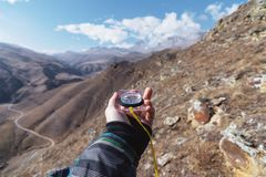 A man`s hand holds a pocket magnetic compass for navigation against the background of a rocky slope and epic rocks under. A blue sky and white clouds. The Stock Photo
