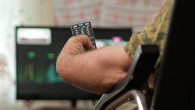 A man`s hand holds the remote from the TV and switches channels. Close-up, moving camera stock video