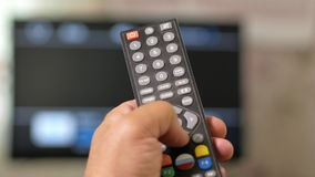 A man`s hand holds the remote from the TV and switches channels. Close-up, moving camera.  stock video