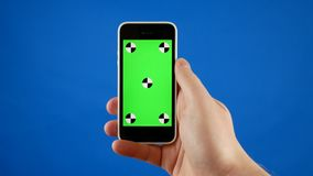 Close up. A man`s hand holds a smartphone with a green screen and makes swiping, touching and scrolling gestures. Blue stock video