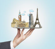A man's hand holds a tablet with sketches of the most famous places in Italy, Great Britain and France. The concept of tourism and Stock Photography