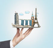 A man's hand holds a tablet with sketches of the most famous places in Italy, Great Britain, France and Singapore. The concept of Royalty Free Stock Photography