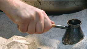 Man`s hand holds Turk and prepares Turkish coffee in the sand in it. Slow motion. Man`s hand holds Turk and prepares Turkish coffee in the sand in it. Slow stock footage