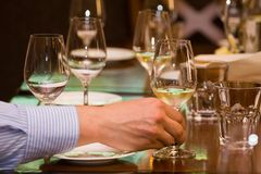 Man`s hand holds a wineglass with white wine during wine testing in a restaurant stock image