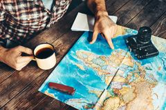 Man`s hand indicates a route on a paper map. Another hand holds a mug of tea. The man is inspired by photography and plans a hike. On a dark wooden table, top Stock Photo