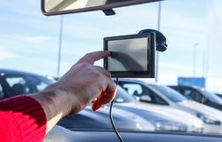 Man`s hand inputting information into GPS in car with parked cars in the background. A Man`s hand inputting information into GPS in car with parked cars in the Stock Photos