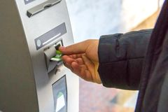 A man`s hand inserts a plastic card into the card receptacle of cash machine. A man`s hand inserts a plastic card into the card receptacle of a gray cash machine royalty free stock image