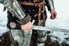 Man`s hand with an iron sword Stock Photo