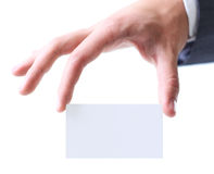 Man's hand keeping a business card among two  fingers. Royalty Free Stock Image