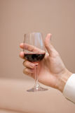 Man's hand keeps a glass. With a red wine on a light background Stock Photography
