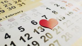 Man`s hand lays out red paper heart on the 14 February month in a calendar. Love holiday for young and old. Man`s hand lays out red paper heart on the 14th stock video footage