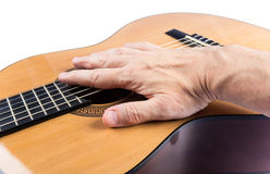 Man's hand lies on body of classical guitar on white Royalty Free Stock Images