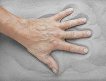 Man's hand lies on the sand Stock Image