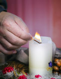 Man's hand is lighting a candle Stock Image