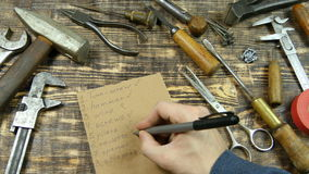 Man's hand list out the tools, flat lay stock video footage