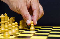 Man's hand making a chess move Stock Image