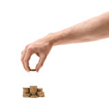 Man's hand making stacks of golden coins Stock Image