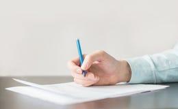 Man& x27; s hand met een pen en een stuk van document Stock Afbeeldingen