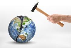 Man& x27; s-Hand mit einem Hammer schlägt die Planet Erde Stockbild