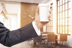 Man& x27; s-Hand mit Kaffee im Café Stockbild