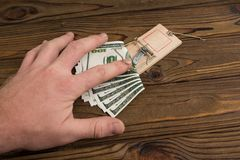 A man`s hand and a mousetrap with bait money dollars banknotes. Concept business risk, collar, bribe. caught stealing stock image