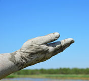 Man& x27;s hand in the mud extended forward. Against the blue sky Royalty Free Stock Photos