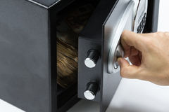 Man's hand opening the door of a safe deposit box Stock Image