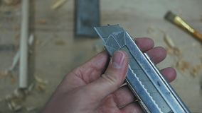 Man`s hand opens the blade of a carpenter`s knife.  stock video