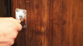 Man`s hand opens a lock with a key in the door.  stock video