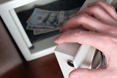 A man`s hand opens the safe door. US dollar bills in a metal box. The concept of saving money in a hotel or bank, crime and theft. Selective focus. Shallow royalty free stock photo