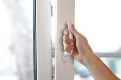 A man`s hand opens a white plastic window. Close up.  royalty free stock photography