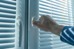 Man`s hand opens window the blinds or jalousie Royalty Free Stock Photos