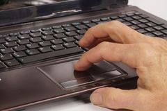 Work on a computer. A man`s hand operating a laptop with the help of a touchpad stock photography