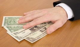 Man's hand over dollars Royalty Free Stock Photos