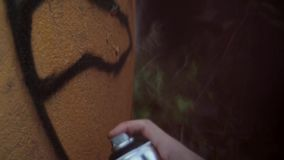 Man's hand paint spraying graffiti on the wall. Summer day.  Close up. Vandalism. Man's hand in millitary cloth paint spraying graffiti on the wall. Summer day stock video footage