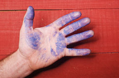 The man's hand painted in blue on red wooden background Stock Image